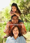 Mexican Family Picture.  A grandfather, grandmother and grandaughter pose for a family portrait.  The cute adorable young mexican child is sitting atop her grandfather's shoulders.  Happy family photos for advertising.