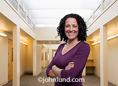 In this portrait a happy woman with here arms crossed stands in a modern upscale and well lit office with an air of confidence and success.