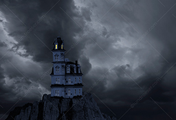 A haunted house sits atop a bluff and under dark storm clouds in a stock photo.