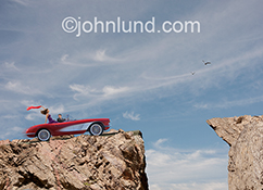 Disaster is about to strike in this stock photo featuring a distracted driver of a convertible sports car about to drive off of a cliff as he ogles his woman passenger.