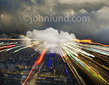 High speed cloud computing is dramatically illustrated in this stock photo of a cloud over a city at night with streaks of light, representing data and information, streaming out towards the viewer.