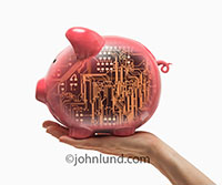 A hand holds up a Piggy Bank with a high-tech circuit board visible within in an image about high tech investment, finance and capital funding.