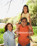 Picture of a Family Outing.  A Mexican or hispanic family outdoors in the sunshine.  Photo shows cute young smiling child, a girl, sitting on her grandpa's shoulders. All are smiling at the camera. Fun family outing pics for ads.