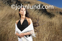 Beautiful Hispanic woman standing on a dry grassy hillside with boulders and rocks sticking up out of the ground. The latina woman is quite beautiful and has long black hair floating in the gentle breeze. Beautiful Latina Women Pix.