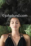 Beautiful sleeping hispanic woman with big hair.  Very attractive Latina woman laying on her back with her eyes closed and her air spread out about her.  Beautiful Latina Woman Pic.