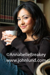 Portrait stock photo of a beautiful young hispanic woman holding a cup of coffee in her hands. Shoulder length black hair and a pleasing grin on her face.  Wearing a dark sweater and blue jeans.