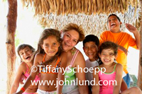 Five hispanic kids and their mother are laughing in this portrait style stock photo of a family having fun under a thatched roof for shade. Fun family photos.