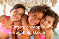 Three young hispanic girls hugging and smiling at the camera.  These kids are wearing bathing suits and must be at a tropical resort. They are under a thatched roof. Cute kid pics.