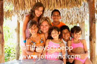 Portrait type photo of a hispanic mother with her six children.  The group photo was taken under a shade with a thatched roof. Fun family vacation photo. Kids are wearing swiming suits.
