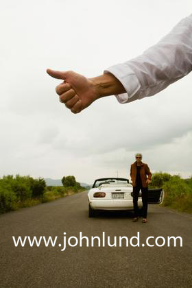 A hitchhikers thumb in the air.  A man is hitch Hiking and just his arm, white shirt sleeve and hand is visible.  Another man stands at the rear of their broken down car.