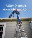 A man using a ladder to climb up onto his roof so he can do some DIY roof repair. Picture of a man climbing onto the roof of his house. Ladder climbing pics.