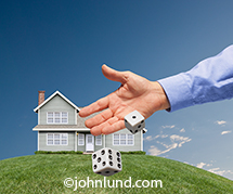 A hand rolls the dice in front of a house on a green grass covered hill in a visual metaphor for gambling on mortgages, real estate agents, real estate market vagaries, home financing and DIY repairs.