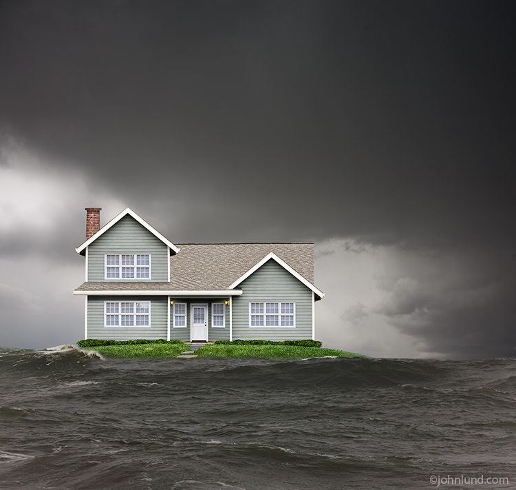 A house is threatened by flood waters as it sits on a grassy hill just above the level of the surrounding water in a visual metaphor not just for the threat of floods, but also of any natural disaster.