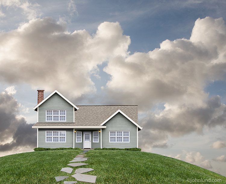 Photo of a beautiful iconic American home on a hill with summer clouds in the background.