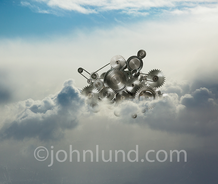How cloud computing works is the concept behind this stock photo of a complex cluster of gears, sprockets and chains emerging from a cloudscape.