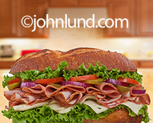 A huge dagwood style sandwich sits on a kitchen counter in an image about abundance and food in this close-up stock photo.