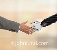 A human businessman and a robot shake hands in a stock photo about robot and human interaction and robot-human integration issues.