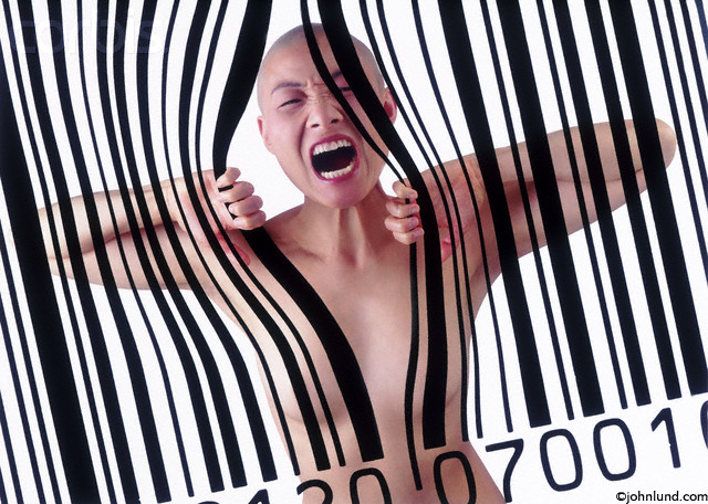 Pictures of a screaming woman trapped in a bar code as if in jail and behind bars. She is Asian and has a shaved head. She is not wearing clothing.