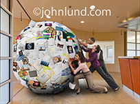 Information management and teamwork are the themes behind this photo of three businesspeople attempting to push a huge ball of papers, pictures and information out the door of their corporate headquarters.