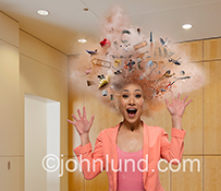 Information overload is dramatically and humorously shown in this stock photo showing a woman with her head exploding in a cloud of dust and objects as she wears an expression of surprise.