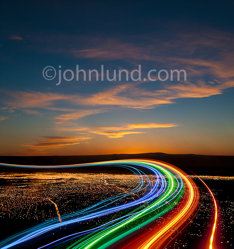 In a stock photo about Internet connections, streaming data, big data, and cloud computing, colored light trails flow gracefully above a city at dusk beneath a dramatic sunset.