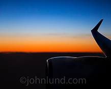 A view of a jet engine through the window at sunrise becomes art in this stock photo about travel, adventure, and possibilities.