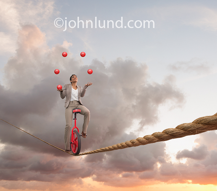 A woman rides a unicycle across a tightrope while juggling red balls in this metaphorical image for multi-tasking.
