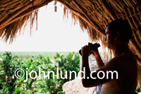 An ethnic man holding a pair of binoculars overlooking a jungle terrain from under a thatched roof. Man binoculars jungle pic.