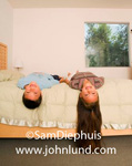A young brother and sister are laying on their backs on a bed with their heads hanging over the side. The little girls hair reaches to the floor. Long brown hair.  The room is white with a window in the background with greenery visible outdoors.