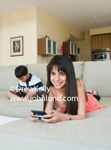 Young girl and her brother at home playing computer games.  Photo of kids playing video or computer games while sitting on the sofa at home. The girl has long black hair and is smiling at the camera.
