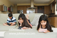Kids playing video games. Three young children laying  on a sofa at home and they are absorbed in the video games they are playing.  Two girls with long hair and a boy further back.