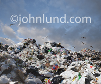 Huge mounds of trash rise up in a mountain of garbage at a landfill site in this image about sustainability, waste management and ecological concerns.