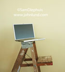 Odd stock photo of an open laptop computer sitting on the top of a old paint covered used wooden step ladder. Interesting advertising photography.