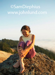 A senior Chinese woman is sitting on a rocky outcrop atop a hill on the Northern California coast.  Blue sky background. Chinese woman is barefoot sitting with knees pulled up to chest.