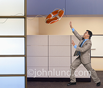 A life ring sales out towards a reaching businessman in a stock photo about rescue and salvation in the business world.
