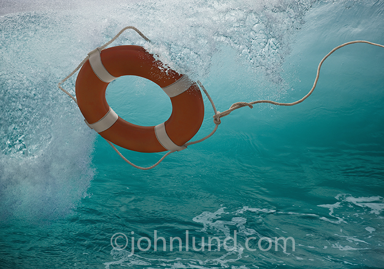 A life ring sales out over a huge breaking wave in an image about hope, salvation, and rescue.
