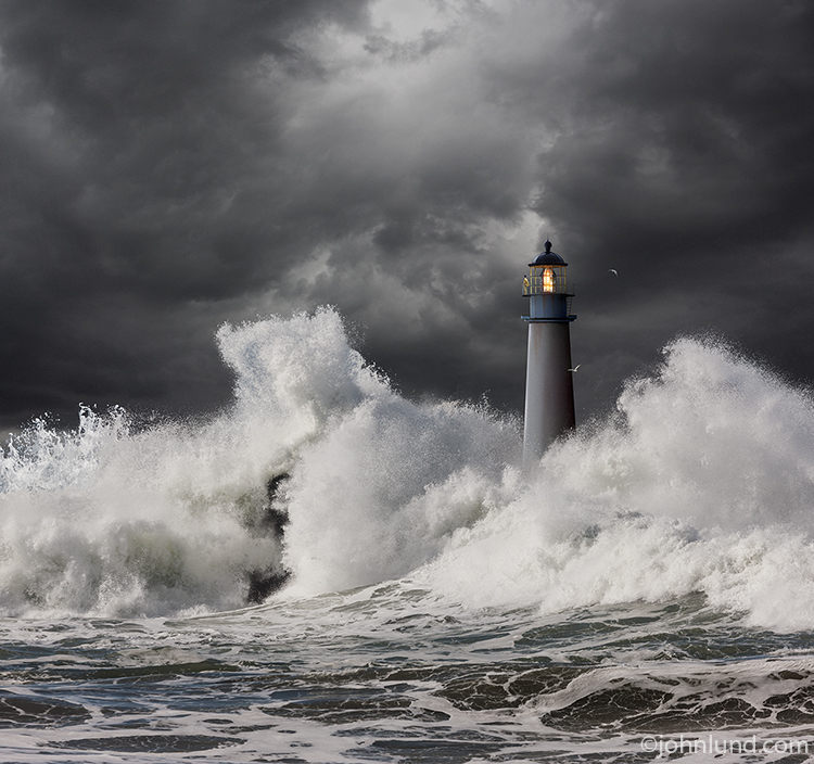 A lighthouse keeper stands watch at the top of a lighthouse while huge ocean waves crash all around as dark storm clouds approach in an image about vigilance, vision, guidance, safety danger and risk.
