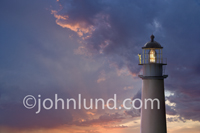 A lighthouse keeper searches the horizon with binoculars as a passing storm leaves a brilliant sunset over the ocean.