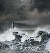 A lighthouse casts its beam across a stormy sea in a stock photo about danger, risk, salvation and navigation.