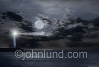 A full moon lights up the night clouds and a lighthouse casts its beam out over the ocean in a bucolic scene