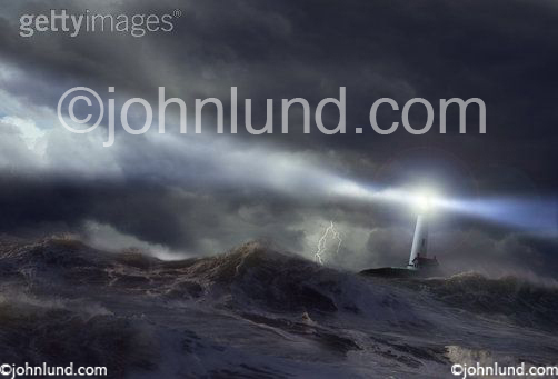 A light house casts a beam over a rough sea in a stock picture about risk, danger, guidance and salvation.