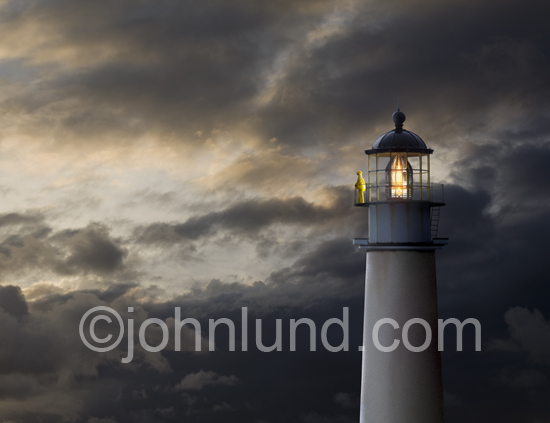 Storm clouds clear as a keeper in wet weather gear searches the ocean from the lamphouse rail of a lighthouse. This photo is a great metaphor for searching the internet as well as a symbol of safety, security, guidance and navigational aid.