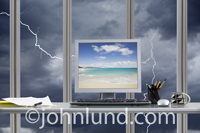 A tropical beach scene is displayed on a computer monitor while outside the office a thunderstorm with lightning strikes rages.
