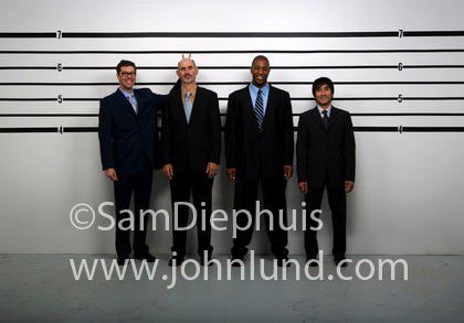 Funny picture of a police line up. The suspects in the lineup are businessmen. Some of the suspects are being silly resulting in a funny police lineup photo. Silly stock photo.