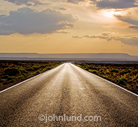 A long, straight road, golden in the sunset light, stretches into the distance in a metaphor for the way forward, the future and new beginnings.