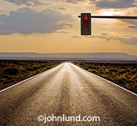 A long, straight road stretches into the distance while overhead a single stop light shines red in a visual metaphor about the challenges, obstacles and delays that often impede progress on the way forward and into the future.