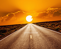 A long straight road stretches to the horizon and a huge round orange ball of a sunset in a stock image about journeys, the future, and the road ahead.