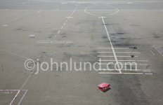 A piece of lost luggage, a red suitcase popping open, lies alone on the airport tarmac, a symbol of loss and challenges.