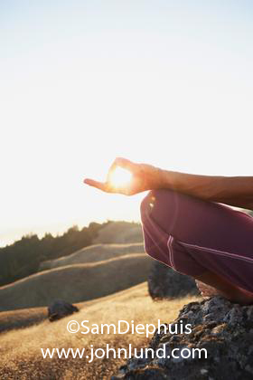 woman sitting in lotus position with sun showing through
