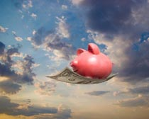 A piggy bank rides a magic carpet of money in this stock photo about financial, investment and savings success.